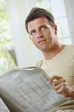 Handsome man reading newspaper at home in casual wear. Stock Photo - 6338824