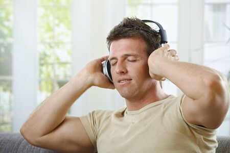 Handsome man  with smile listening to music on headphones with eyes closed in casual wear. Stock Photo - 6338710