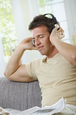 Handsome man  with smile listening to music on headphones with eyes closed in casual wear. Stock Photo - 6338763