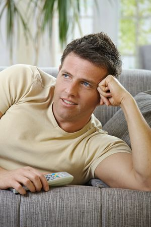 Handsome man in causal wear smiling lying on sofa with remote control handheld, watching television Stock Photo - 6338837