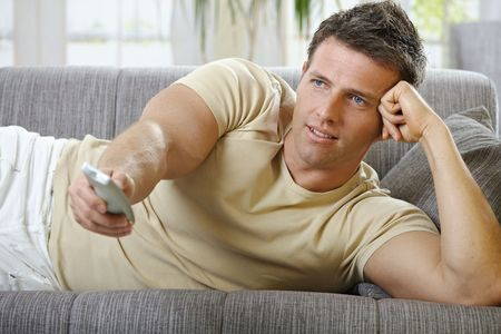 Handsome man in causal wear smiling lying on sofa with remote control handheld, watching television Stock Photo - 6338878