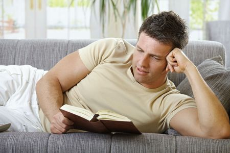 Handsome man in causal wear smiling lying on sofa reading handheld book. Stock Photo - 6338881