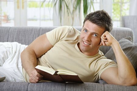causal: Handsome man in causal wear smiling lying on sofa reading handheld book.