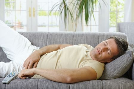 lying in front: Goodlooking man in causal wear sleeping on sofa. Stock Photo