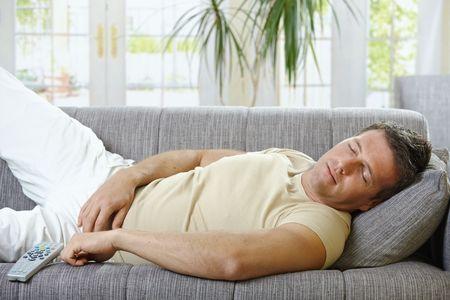 causal: Goodlooking man in causal wear sleeping on sofa. Stock Photo