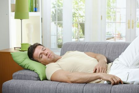 Goodlooking man in causal wear sleeping on sofa with remote control in hand. photo