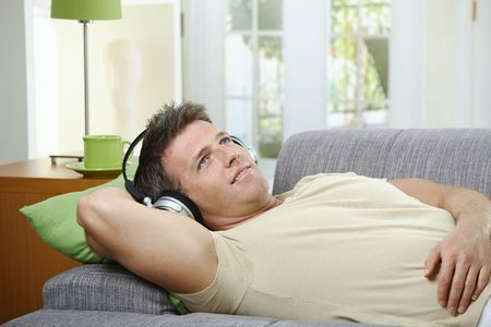 Handsome man with smile listening to music on headphones lying on couch. Stock Photo - 6338865