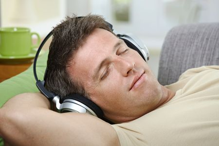 Goodlooking man with eyes closed smiling listening to music on headphones. photo