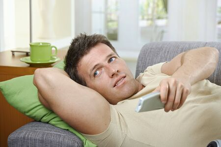 Goodlooking man in causal wear smiling on sofa using remote control. Stock Photo - 6338859