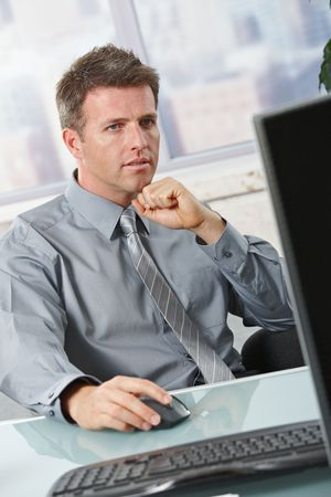 Determined businessman concentrating on computer task sitting in office. Stock Photo - 6338722