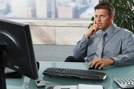 Confident businessman focusing on computer screen sitting at desk in office. Stock Photo - 6338868