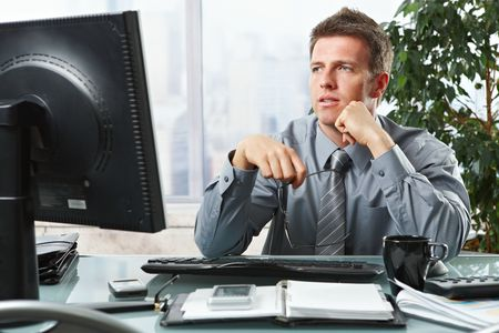 Confident businessman focusing on computer screen sitting at desk in office. photo