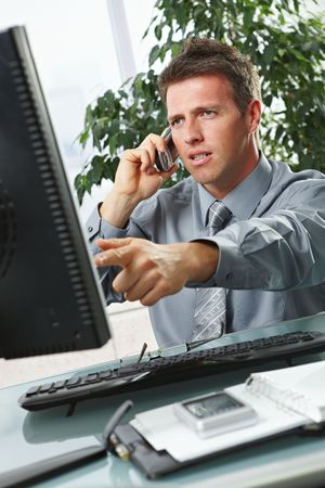 Troubled businessman pointing at screen disussing work on mobile phone sitting at office desk. photo