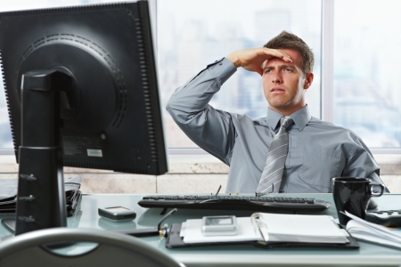 employment issues: Serious mid-adult businessman reading report on computer screen looking worried and occupied with hand raised to forehead. Stock Photo
