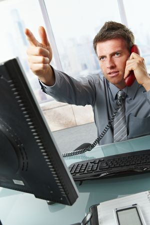 Serious businessman talking on landline phone gesturing out of picture sitting at office desk. photo
