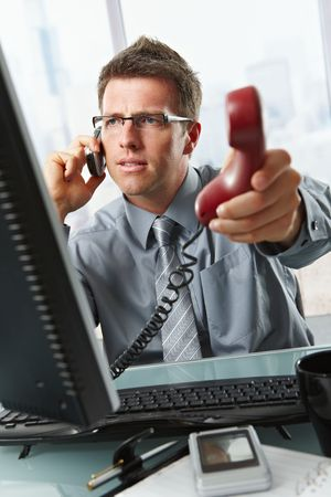 Businessman with glasses busy talking on mobile phone handing over landline call to answer in office. photo