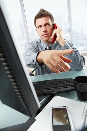 businessman talking: Serious businessman talking on landline phone gesturing out of picture sitting at office desk.