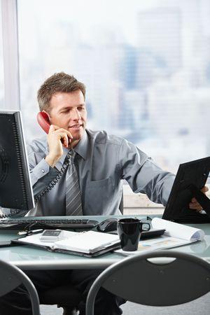 Happy businessman having conversation on landline phone looking at family photo smiling.