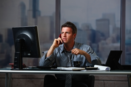 late: Tired businessman on call  working late holding glasses looking at screen doing overtime in office at night. Stock Photo