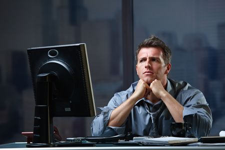 Determined businessman concentrating hard on difficult computer task working late in office looking worried. photo
