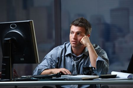 Tired professional businessman looking at computer screen troubled, thinking at office desk working overtime.