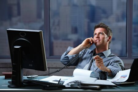 Mid-adult successful smiling businessman calling on landline listening to conversation sitting at office desk. photo