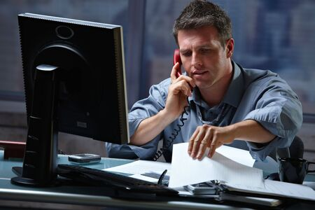 working overtime: Mid-adult businessman speaking on landline phone working overtime in office checking papers.