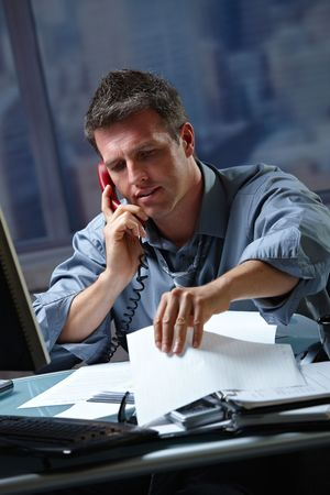 Mid-adult businessman speaking on landline phone working overtime in office checking papers. Stock Photo - 6338730