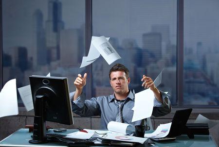 Entrepreneur épuisé projetant des documents à air assis au comptoir de bureau dans les heures supplémentaires. Banque d'images