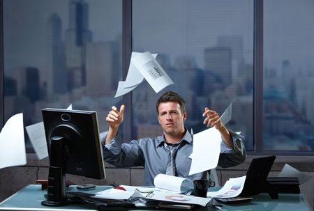 worried businessman: Exhausted businessman throwing documents into air sitting at office desk in overtime. Stock Photo
