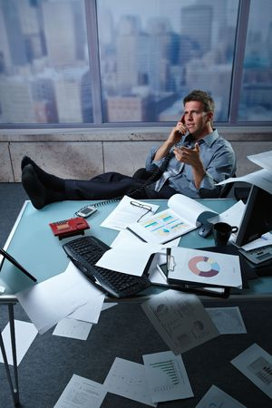 Tired businessman calling from office with shoes off fees up on table papers lying all around, picture taken from high angle. Stock Photo - 6338809