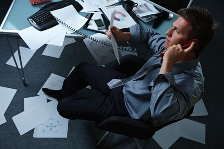Tired businessman calling from office with shoes off papers lying all around, picture taken from high angle. Stock Photo - 6338833