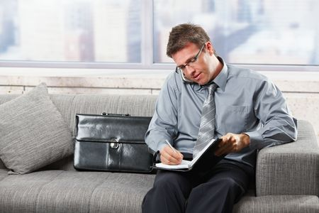 taking note: Imprenditore males tenendo note organizzatore mentre parla sul telefono mobile, seduta sul divano.