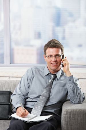 Handsome businessman talking on mobile phone smiling seated on couch. photo