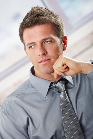 Portrait of confident businessman looking aside with small smile leaning on chin. photo