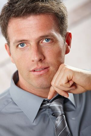 Portrait of confident businessman looking at camera with small smile leaning on chin. photo