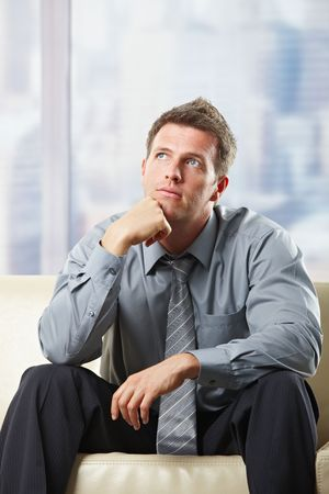 Handsome professional thinking seated on beige sofa looking up in pose. photo
