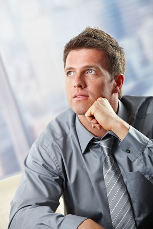 Portrait of confident businessman looking up leaning on hand thinking. photo