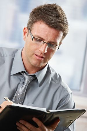 Mid-adult professional businessman with glasses taking notes into organiser sitting on couch. photo