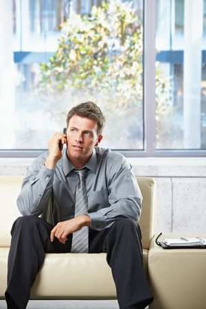 Elegant professional listening to call on cell phone sitting on beige leather sofa in sunlit room. photo