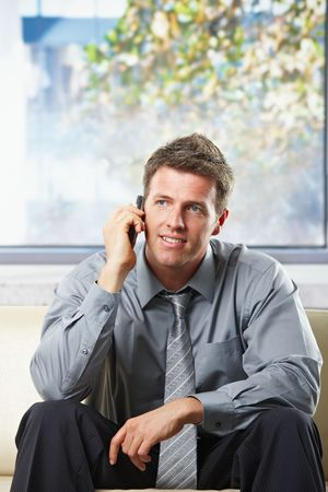 Happy professional businessman getting good news on mobile phone smiling on a sunlit sofa. photo