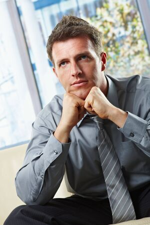 Portrait of sitting businessman focusing looking up with face leant on fists  in sunlit room. photo