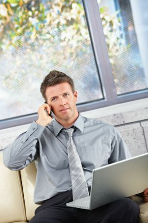 Businessman on cell phone sitting on a beige sofa with computer in lap. Stock Photo - 6338872