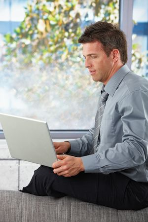 Mid-adult businessman using laptop computer sitting casually on couch in sunlit room. Stock Photo - 6338839