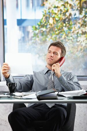 Smiling professional businessman on landline call looking at paper held in hand siting at office desk. photo