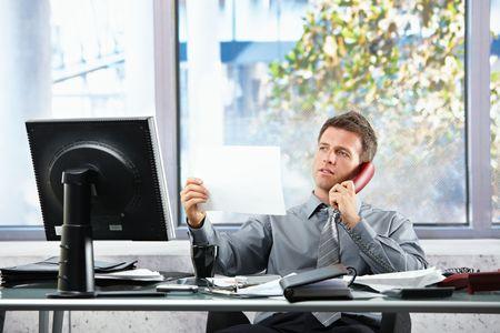 llamando: Sonriendo a empresario profesional en las llamadas de tel�fono fijo mirando de papel que se celebr� en la mano emplazamiento en el escritorio de la Oficina.