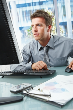 only adults: Mid-adult businessman concentrating on computer work at office desk looking at screen. Stock Photo