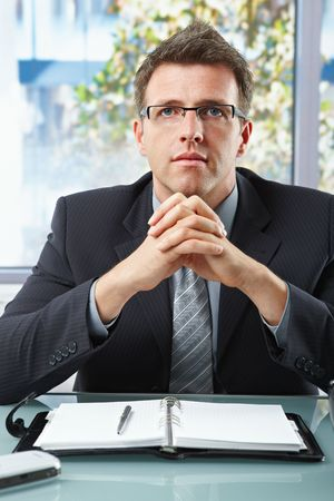 Successful executive businessman wearing suit and glasses looking at camera with hands folded. Stock Photo - 6338823