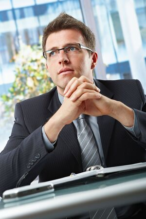 Confident businessman wearing suit and glasses looking aside with hands folded over oraniser in office. Stock Photo - 6338867