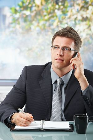 calling businessman: Executive businessman focusing on mobile call taking notes into personal organiser sitting in office.